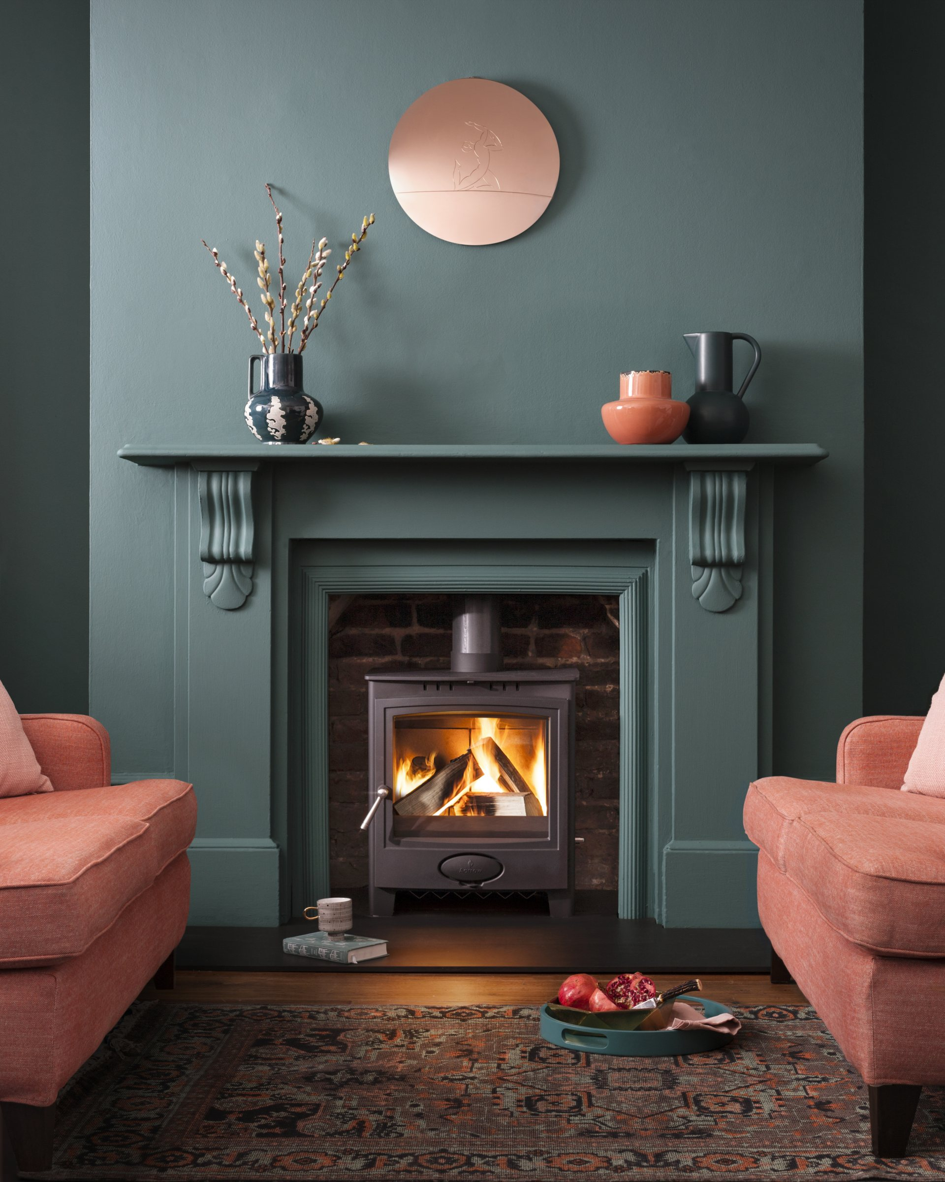 Ecoburn Plus 5 Widescreen stove in lit in fireplace in modern room with green walls and peach-coloured sofa and armchair